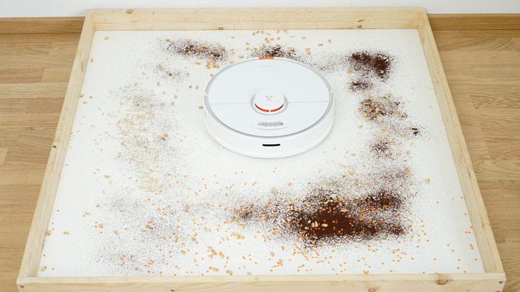 Saugroboter saugt Schmutz im Viereck auf.